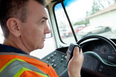 Truck driver holding a radio handset inside the truck