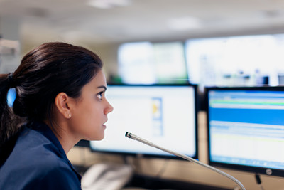 Woman in a control room looking at screens