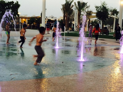 Children enjoying the water play area in Mushrif Central Park.