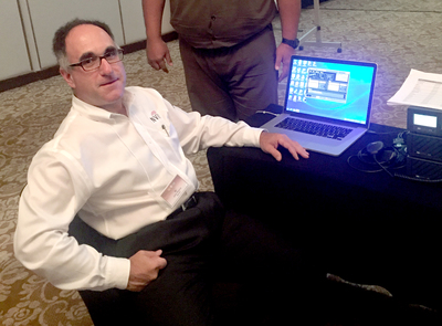 John Rosica, sitting in front of a laptop computer