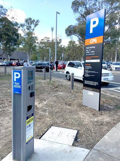 A modern parking meter in a car park