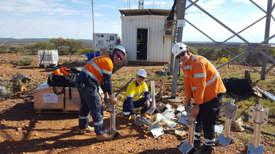 Workers erecting radio gear at the base of a radio tower