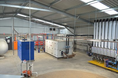 View of the plantroom showing all heating units. Left to right: cogeneration unit, ground source heat pump and gas boiler packs.