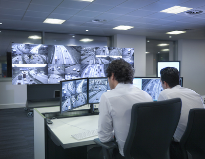 A man looking at CCTV screens of road traffic