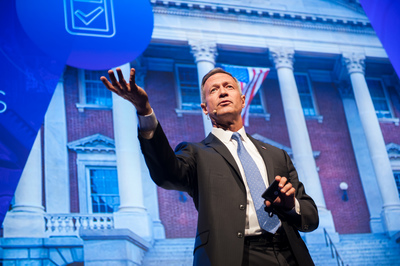 Martin O'Malley on stage giving a presenation, gesturing