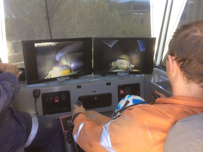 Operators looking at computer monitors inside a remote cabin controlling underground mining equipment
