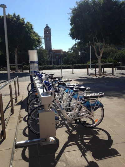 Five e-bikes parked at a charging station adjacent to a Newcastle street