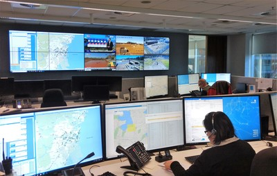 Inside Jemena's control room, showing people working at desks and looking at large computer display screens