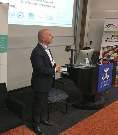 Steven Tsikaris, standing at the front of a lecture room, speaking at the briefing