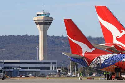 Perth air traffic control tower with two Qantas aircraft tails in the foreground