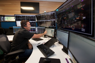 A man at a desk with multiple computer monitors in front of him, in the Powerco Network Operations Centre