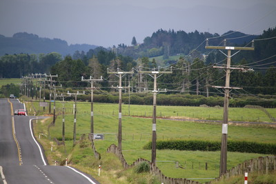 Looking along a road disappearing in the distance, with electric power lines lining the side of the road