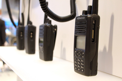 Handheld radios lined up on a bench