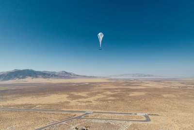 A Project Loon high-altitude balloon floating above a desert