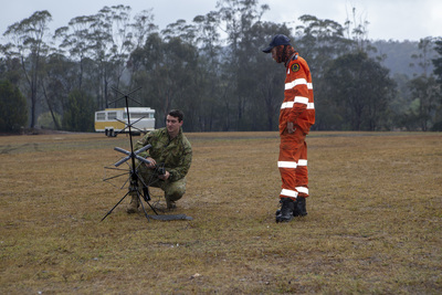 A soldier sets up a satellite communications antenna in a field
