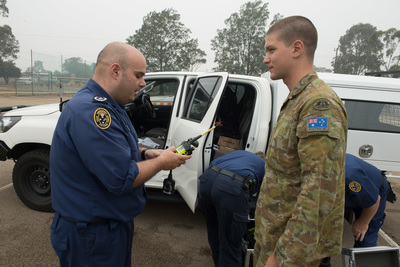 An SES volunteer hands over radios to an Army soldier