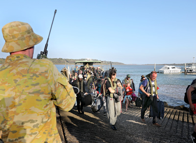 A soldier holds a radio as evacuees disembark a landing craft