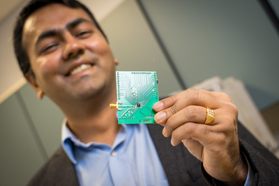 Dinesh Bharadia holds a PCB onto which the Wi-Fi radio is mounted